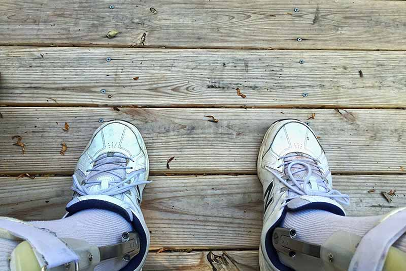 Picture of a pair of feet standing ona wooden deck wearing calipers