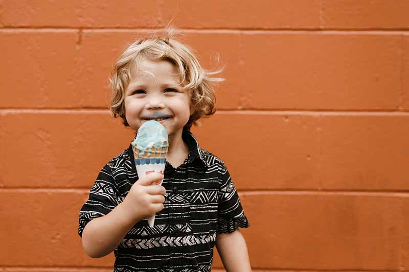 Ppicture of a small child eating icecream against an orange wall