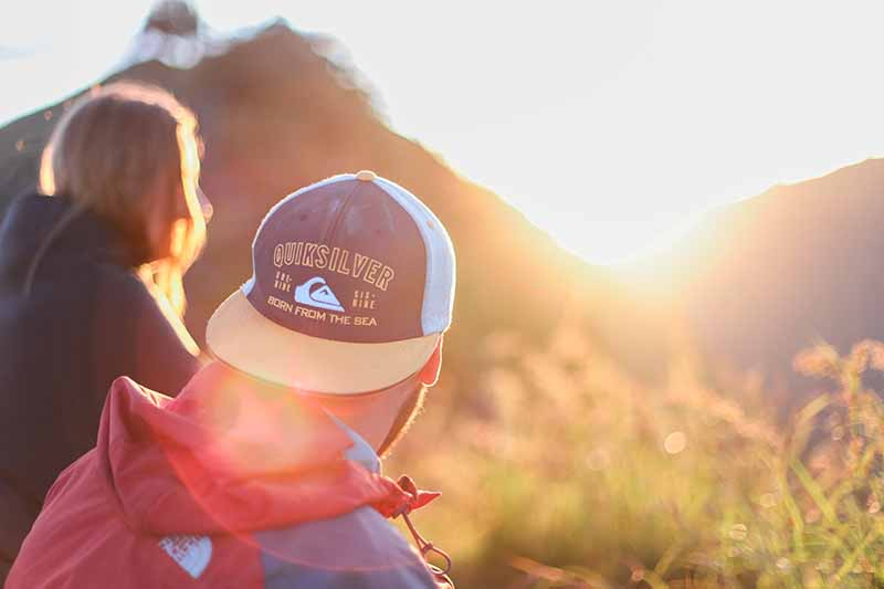 Picture of two men in baseball caps sitting in nature looking at a sunset