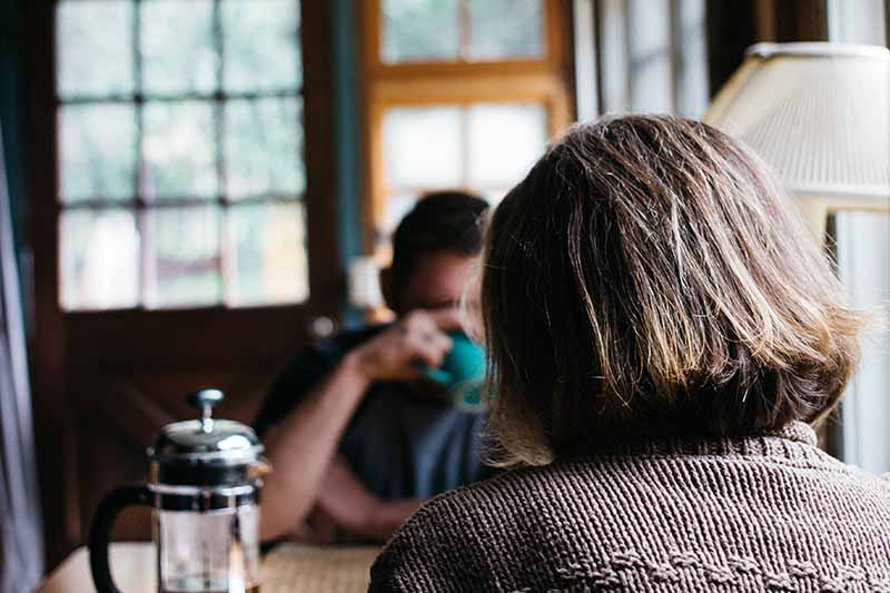 Picture of a lady in brown jumper siting at the breakfast table with her husband