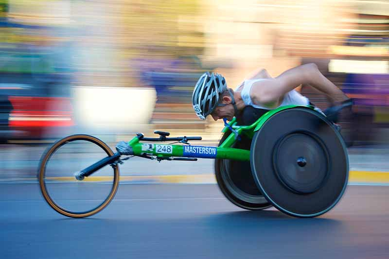Picture of speed racing para athlete on a green wheelchair bike