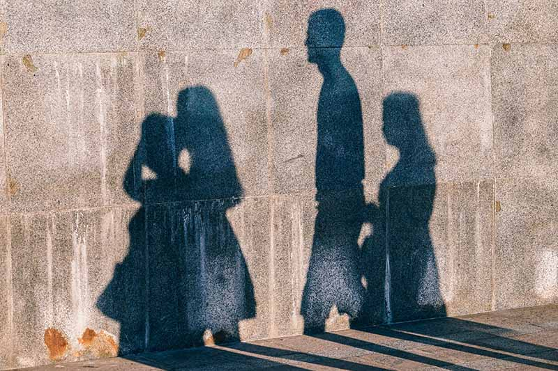 Picture of the shadow of a family walking in front of a wall