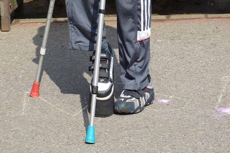 Picture of a mans feet with crutches and chalk drawings on the pavement