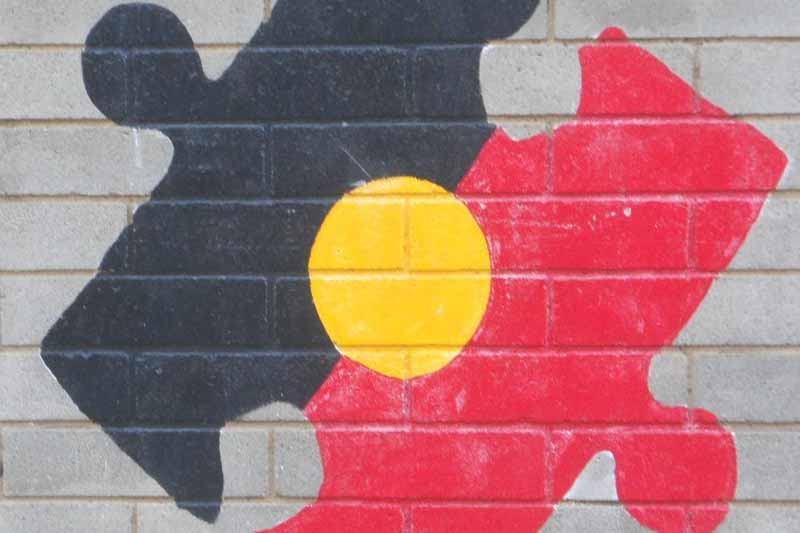 Picture of an aboriginal flag painted on a wall in the shape of a jigsaw puzzle peice