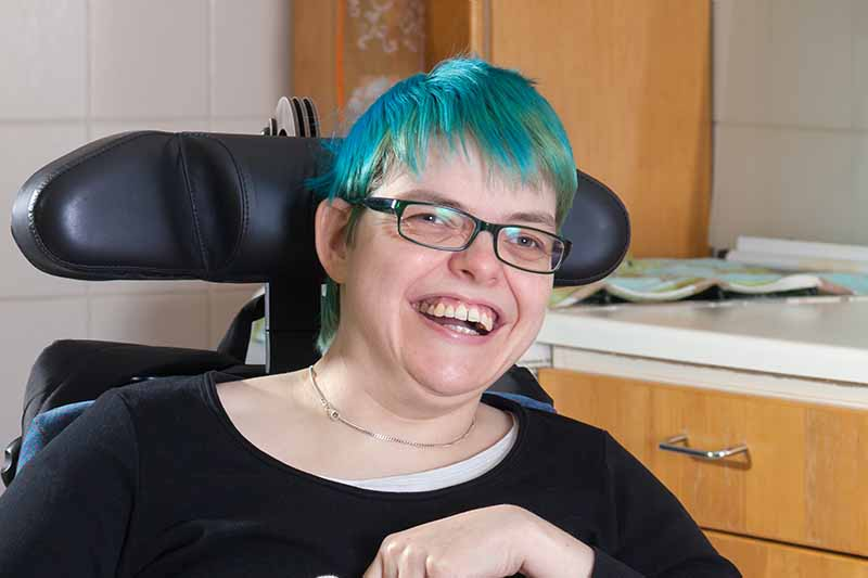 Picture of lady in a wheelchair laughing with green hair