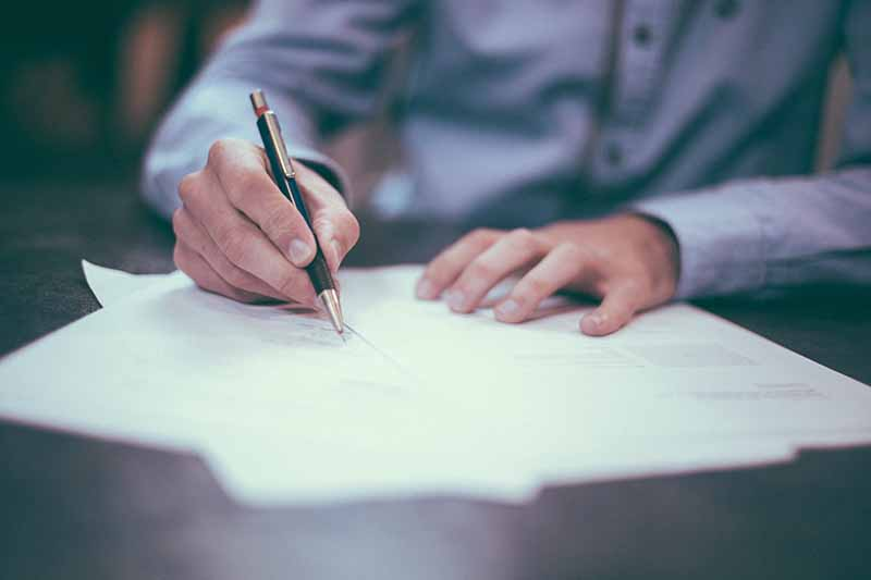 Picture of a lawyers hands signing documents