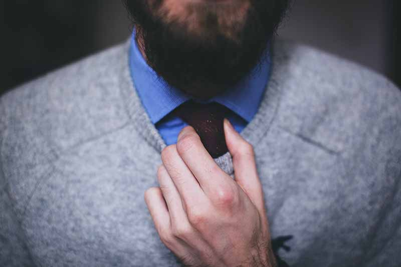 Picture of man with a beard adjutsing his tie