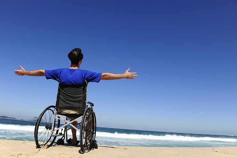 Picture of a man with arms outstetched at the beach with blue sky