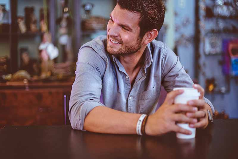 Picture of a guy sitting at a cafe smiling