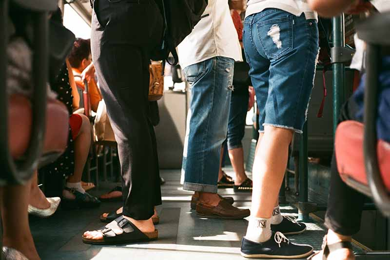 Picture of peoples legs standing on a pubic bus