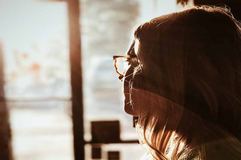 Picture of a woman with glasses gazing out a window with sunlight