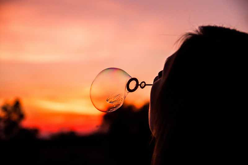 Picture of a girl blowing bubbles in the light of a sunset