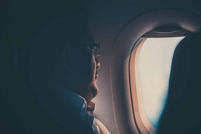 Picture of a man gazing out the window of an aeroplane