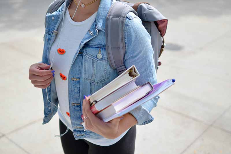 Picture of a girl in a denim jacket carrying text books