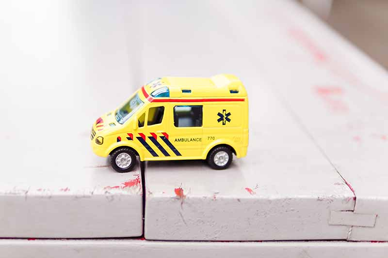 Picture of toy ambulance sitting on a park bench