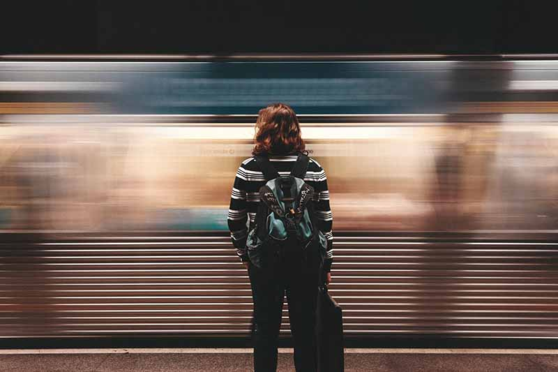 Picture of a lady on a train platform with the train going past very fast