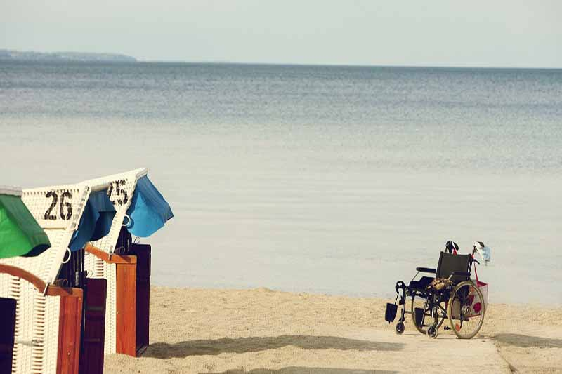 Picture of wheelchair at the beach with coloured beach houses