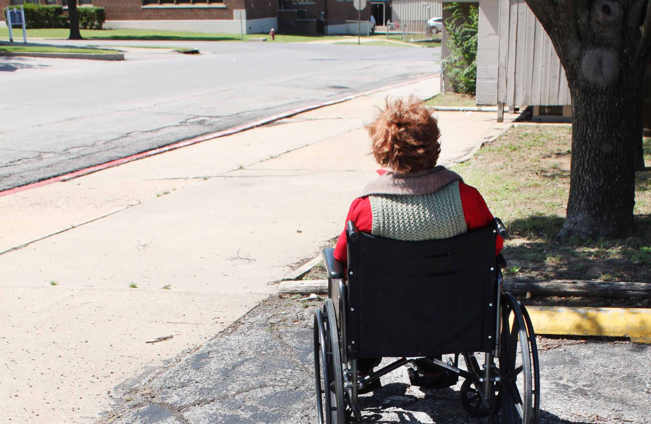 Picture of a woman wearing a red top sitting in a wheelchair at the front of a resifential care facility