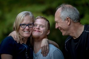 Picture of mother and father with thier son who lives with a disabilty, laughing in the park
